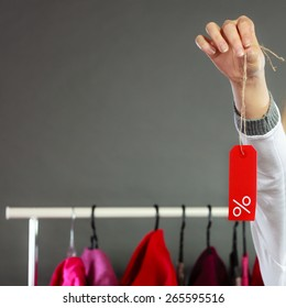 Good shopping sale concept. woman choosing clothes holding discount red label with percent sign in hand