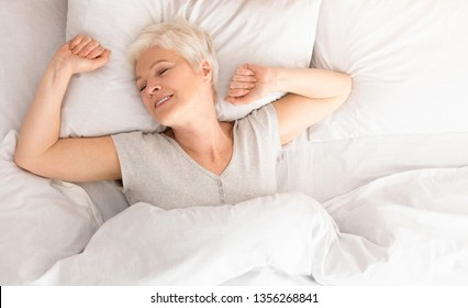 Good sleep. Pleased senior woman stretching in bed, awakening morning moment, top view, panorama with empty space