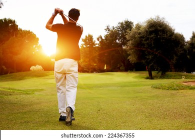 Good strike, golfer swinging his driver and looking away while standing on golf course, professional golfer looking trajectory of the ball, golfer hitting golf ball standing on course at sunny evening