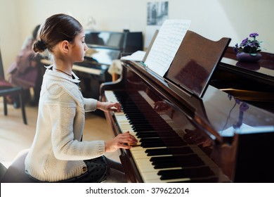 good student plays the piano at a music school