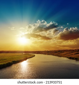 good sunset with rays in clouds over river