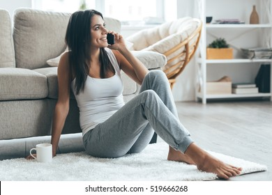 Good talk with boyfriend. Attractive young woman talking on mobile phone and smiling while sitting on the carpet at home