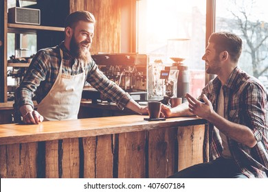 Good talk with customer. Barista and his customer discussing something with smile while sitting at bar counter at cafe