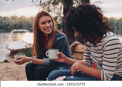 Good talk with friend. Two young beautiful women in casual wear smiling and talking while enjoying camping near the lake