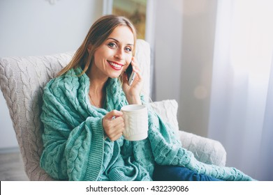 Good talk.Technology and coziness. Beautiful young woman with cup of tea talking by smart phone while sitting on armchair at home