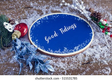 Good Tidings Written In Chalk On Blue Chalkboard Holiday Sign Background With Snow And Decorations.