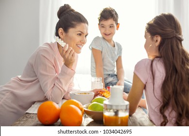 Good vitamins. Attractive smiling dark-haired young mother holding vitamins and talking with her kids about healthcare and the boy sitting on the table