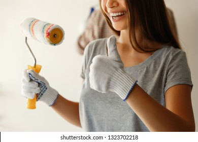 Good work of painters. Happy couple after painting wall with paint roller