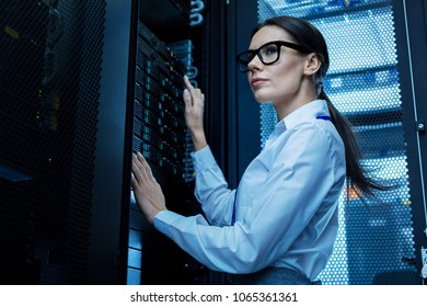 Good working day. Determined pretty woman working with server equipment and wearing glasses