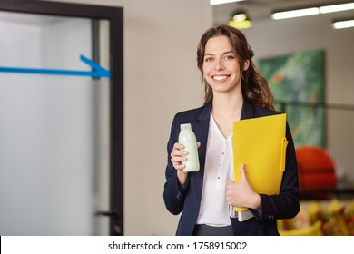 Good working day. Slender young woman standing in office with a small bottle of milk, hugging a yellow folder.