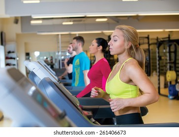 Good workout. Portrait of young and pretty sports girl. Sportswoman is running on treadmill