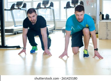 Good workout. Professional trainer and client in a fitness gym are having training