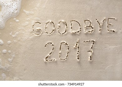 Goodbye 2017 New Year concept hand drawn on beach sand with lapping surf about to obliterate the writing