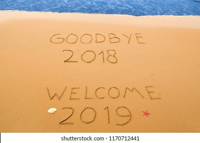 goodbye 2018 and welcome 2019 written in the sand on a sunny beach near the surf