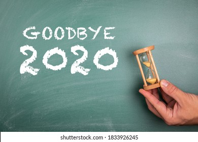 GOODBYE 2020. Annual report, new year's expectations, planning and goals concept. Sandglass in hand. Chalk board