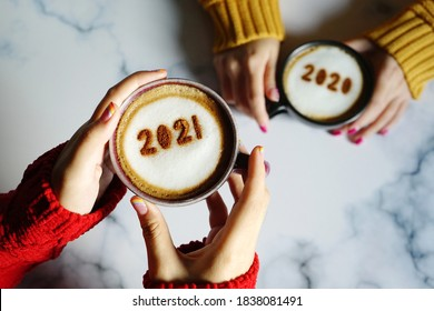 Goodbye 2020, Hello 2021 theme coffee cup with number 2021 on frothy surface in female hands holding and another one with number 2020 on frothy surface over marble table background. Holidays food art.