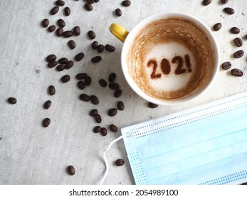 Goodbye 2021 and COVID-19, a year many want time to flies by. Holidays food art theme coffee cup with number 2021 at bottom of cup on cement background with disposable medical mask and coffee beans.