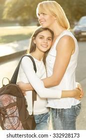 Goodbye hugs. Beautiful woman hugs her teen daughter goodbye before school