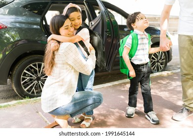 Goodbye mom and dad. Happy little siblings carrying backpacks while holding hands and hugging their parents before going to school
