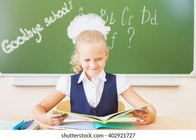 Goodbye school! Girl reading book and sitting at the desk at school