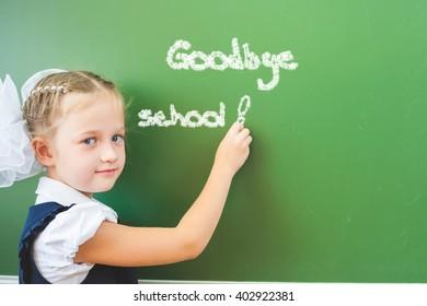 Goodbye school! Schoolgirl writes with chalk on blackboard