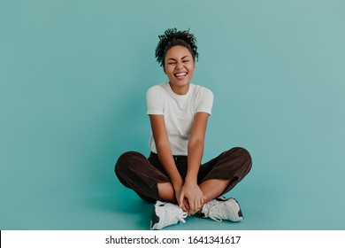 Good-humoured african american girl sitting with crossed legs. Front view of wonderful black female model posing on turquoise background.