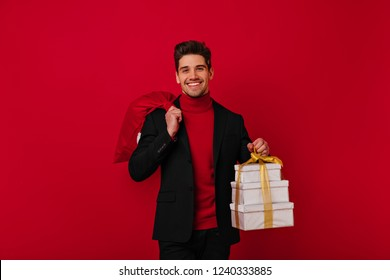 Good-humoured boy holding new year presents for his family. Indoor shot of well-dressed white man preparing for christmas in studio.