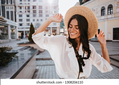 Good-humoured brunette lady posing on city background in hat. Outdoor portrait of attractive dark-haired girl standing on the street.