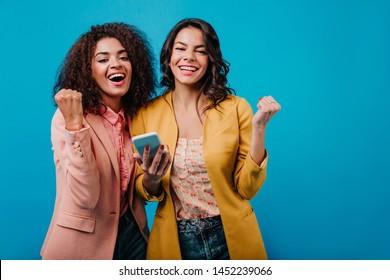 Good-humoured girls having fun together. Studio photo of amazing female models with phone.