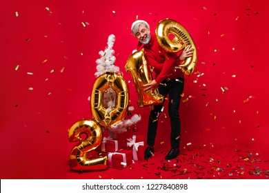 Good-humoured old man celebrating 2019 new year with smile. Studio shot of grey-haired laughing male model enjoying christmas time.