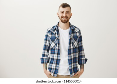 Good-looing confident adult boyfriend with flesh-tunnels and beard standing in blue plaid shirt over gray background, smiling friendly and joyfully, holding hands in pockets