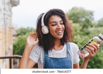 Good-looking african young woman with no makeup having fun with favorite music outdoor. Close-up portrait of blissful curly girl in headphones holding bottle of water on blur background and smiling.