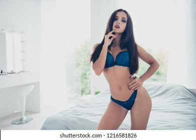 Good-looking alluring dream dreamy magnificent pretty attractive exquisite delicate nude lady in blue underlinen hold hand on waist look at camera stand in cozy light bright room interior