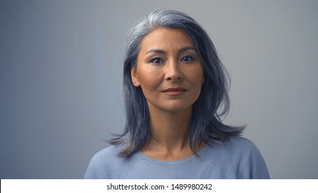 Good-looking Asian Woman In A Light Sweater Is Posing In Front Of The Camera.She Is Serious And Concentrated.Close-up Shot