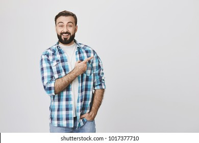 Good-looking bearded adult in casual plaid shirt with one hand in pocket pointing right with index finger, lifting eyebrows and smiling cheerfully against gray background