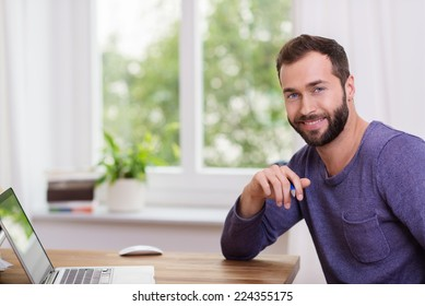 Good-looking bearded man in a home office sitting at a table with his laptop computer turning to smile at the camera
