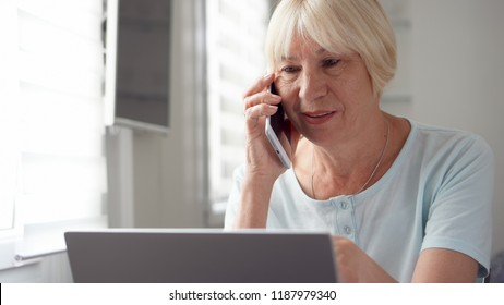 Good-looking blond senior woman sitting at home with laptop and smartphone. Using cellphone discussing project on screen. Remote freelance work on retirement, active modern lifestyle of older people