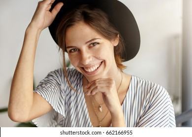 Good-looking brunette woman in black hat holding her hand under chin and on hat having magic sincere smile being happy to recieve proposal from her boyfriend. Positive emotions and beauty concept