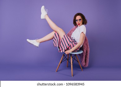 Good-looking caucasian girl with bright makeup sitting on chair. Relaxed female model in white shoes posing on purple background and waving legs.