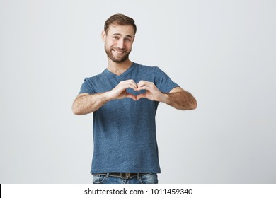Good-looking caucasian male with beard holding hands in shape of heart, symbolizing love, peace and unity. Smiling man in casual clothes showing heart-shaped hand gesture expressing his affection