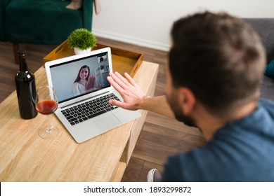 Good-looking couple in love is having a video call at home and are trying to touch hands trough the screen