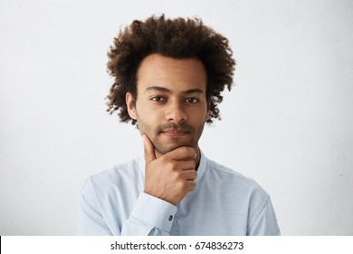 Good-looking dark-skinned male with curly hair having pensive expression holding hand on chin. Young elegant businessman planing his business project looking seriously into camera isolated over white