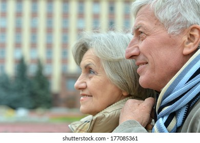 Good-looking elderly couple standing at wall