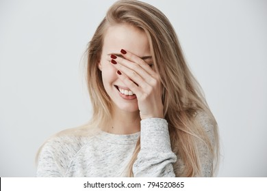 Good-looking emotional young Caucasian woman with blonde long hair, closing eyes with hand while laughing out loud, happy with good positive news, smiling broadly, showing straight white teeth