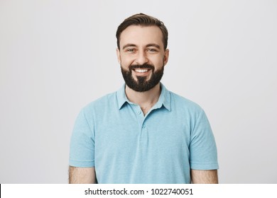 Good-looking european male adult with beard and moustache smiling broadly over gray background. Boyfriend stand behind door, knocks and waits till girlfriend will open it