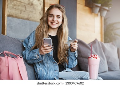 Good-looking fair-haired girl in trendy denim jacket sitting and relaxing in cafe, holding smartphone and credit card, wanting to pay for delicious cocktail, smiling cheerfully at camera