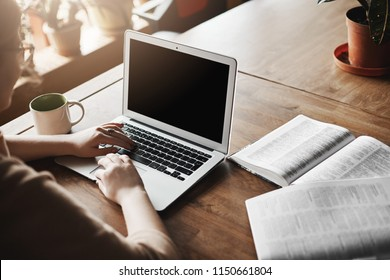 Good-looking female researcher sitting in cafe, working out of office, drinking coffee, taking break, browsing internet, checking social media and relaxing, messaging friend to make appointment