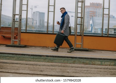 Good-looking gentleman holding travel suitcase and striding down the sidewalk stock photo