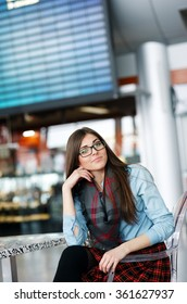 Good-looking girl with beautiful long brunette sitting on the transparent chair at the cafe, smiling into the camera.