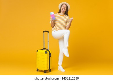 Good-looking girl feeling joy of buying tickets for vacation, isolated on yellow background